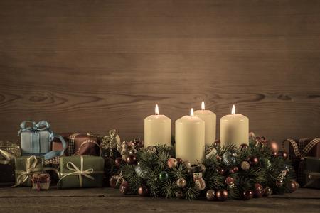 corona de adviento: Corona de Adviento, o corona con cuatro velas encendidas y regalos para un bono. Foto de archivo
