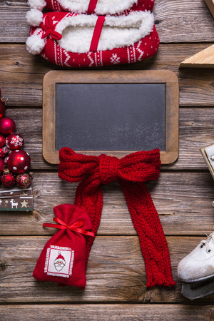 christmas promotion: Christmas or advent wooden sign or blackboard with red decoration for a greeting card.