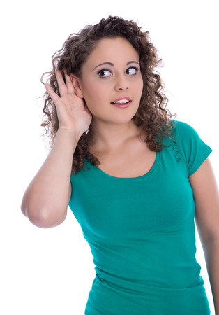 Isolated young funny woman in green listening for special sales offers or is suffered of deafness.