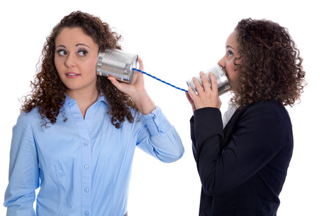 Communication concept: two isolated business woman talking with tin can over white background.