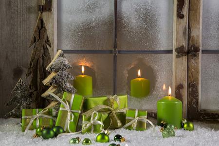 Groene houten kerst decoratie in een etalage met cadeautjes en kaarsen. Stockfoto