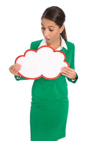 advertising signs: Shocked isolated professional business woman wearing green suit holding white and empty sign for advertising in her hands.