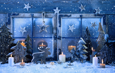 Outdoor advent window decoration in blue color with wood and burning candles.