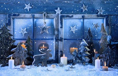 Outdoor komst raamdecoratie in blauwe kleur met hout en brandende kaarsen. Stockfoto