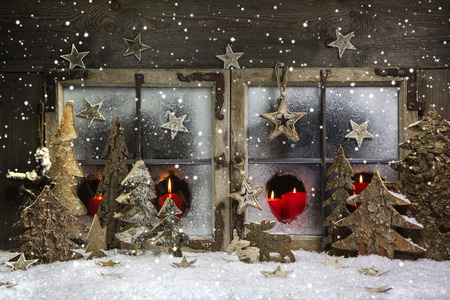 Atmospheric and romantic christmas window decoration with red candles, snow and wood.