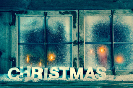 Atmospheric old christmas window with red candles and text for decoration. photo