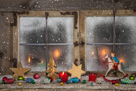 Festive decorated wooden christmas window with candles and vintage decoration.