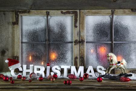 country: Rustieke houten kerst venster met rode kaarsen, paard en groet tekst.