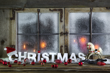 Rustic wooden christmas window with red candles, horse and greeting text.