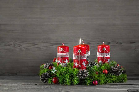 Advent wreath or crown with four red candles on wooden grey background.