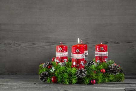 Corona de Adviento, o corona con cuatro velas rojas sobre fondo gris de madera. Foto de archivo - 31732996