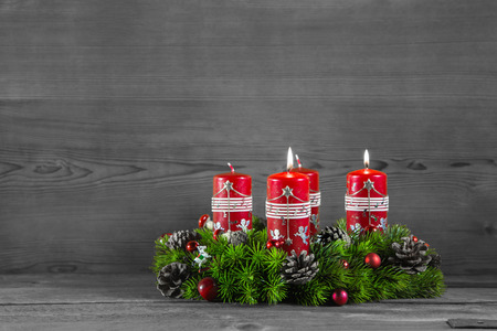 Advent wreath or crown with four red candles on wooden grey background. photo