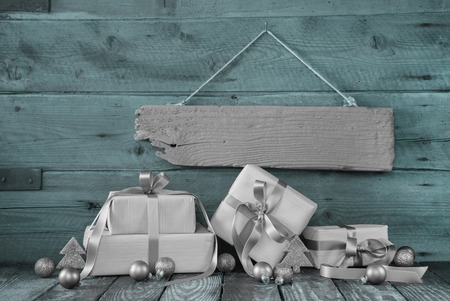 Silver christmas presents on wooden background with a sign for a bonus card. photo