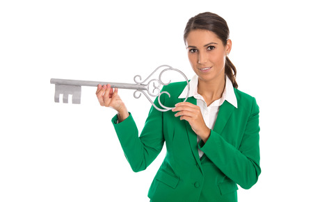 housewarming: Isolated businesswoman in green holding key for dedicate a house or making housewarming party.