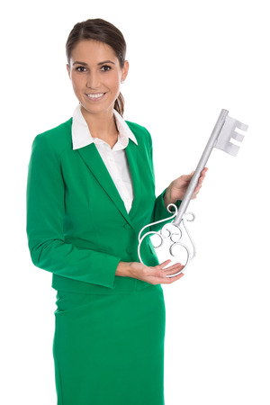 Isolated businesswoman in green holding key for dedicate a house or making housewarming party. photo