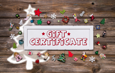 Wooden colorful christmas signboard with text and decoration: gift certificate. photo