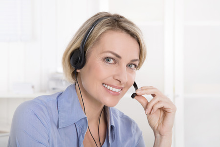 Attractive souriant femme d'âge moyen en blouse bleue appelant avec un casque.