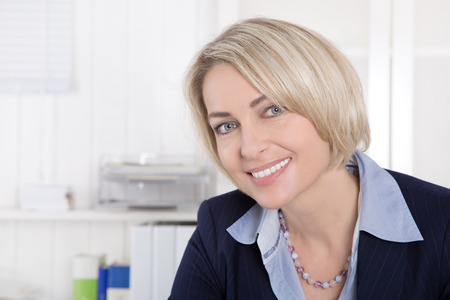 older age: Attractive happy middle aged woman in business outfit sitting in her office.
