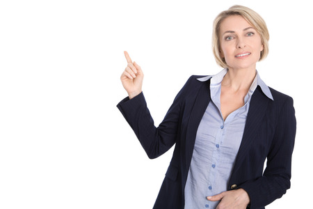Isolated middle aged business woman pointing at white with finger wearing blazer and blue blouse.