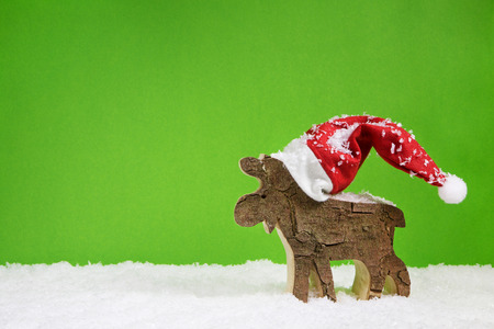 Merry christmas greeting card with reindeer in green red and white colors.