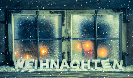 christmas illuminations: Atmospheric vintage xmas window for a background with german text: Christmas. Stock Photo