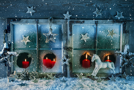 christmas illuminations: Atmospheric christmas window with red candles outdoor with snow. Stock Photo