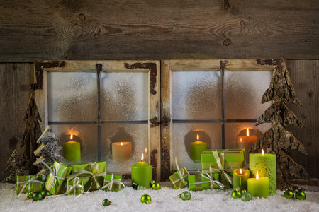 atmosphere: Rustic christmas window decoration in green colors with presents and candles.