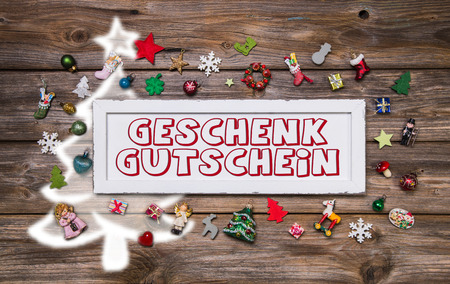 Wooden colorful christmas sign with text and decoration: gift certificate in german. photo