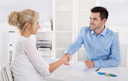 Handshake: Adviser says hello to his female customer sitting at desk. Stock Photo