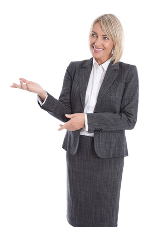 sideways: Older or mature isolated businesswoman presenting over white with hand. Stock Photo
