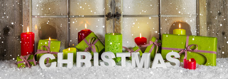 ambiance: Christmas window decoration for advertising or sales in red and green colors with text, presents and candles. Stock Photo