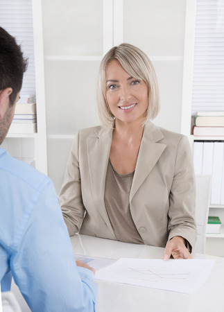career counseling: Successful and smiling middle aged businesswoman in leading position sitting at desk with a colleague. Stock Photo