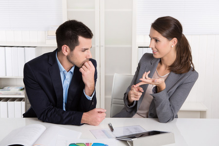 financial adviser: Successful young consultants working as business team in an office analyzing documents.