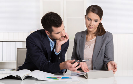 financial controller: Successful young consultants working as business team in an office analyzing documents.