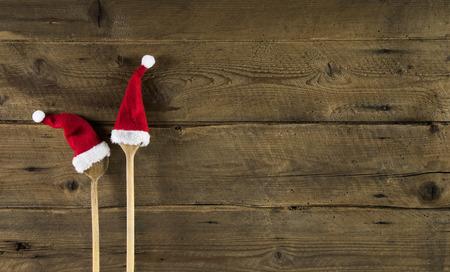 Fond de Noël en bois drôle pour une carte de menu avec une cuillère en bois et deux rouges chapeaux de Père Noël.