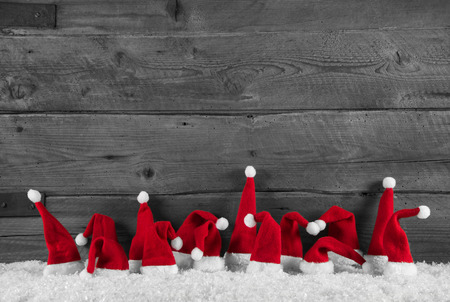 Humorously red, grey and white wooden christmas background with santa hats for a frame.