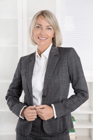 blazer: Attractive smiling senior business woman in portrait wearing blazer and blouse. Stock Photo