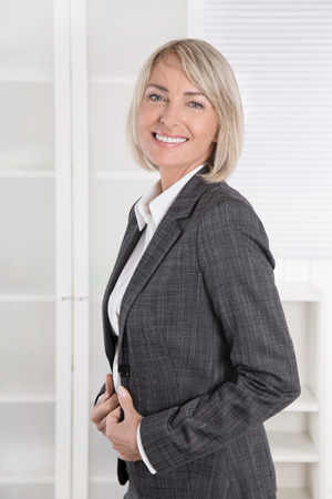 age: Attractive smiling senior business woman in portrait wearing blazer and blouse. Stock Photo