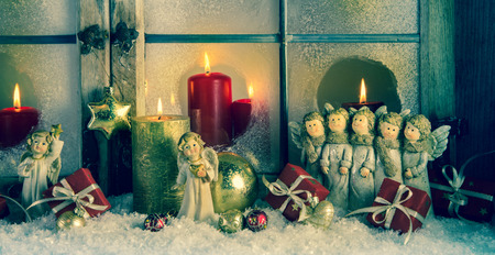 Atmospheric classic christmas decoration with angels, presents and red candles in an old wooden window. photo