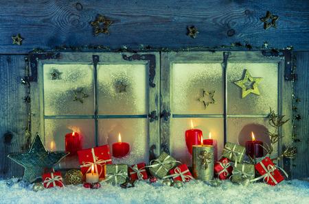 Oude houten raam versierd voor kerst met rode kaarsen en geschenkdozen voor een wenskaart. Stockfoto