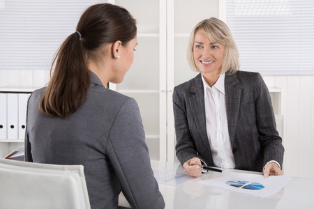 financial controller: Two business woman sitting at desk: customer and adviser talking together.