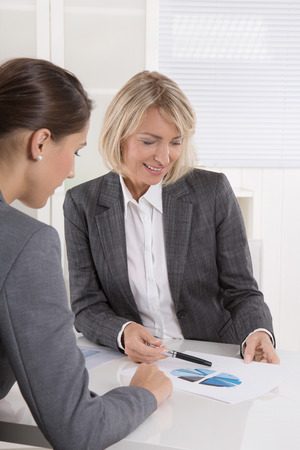 career counseling: Two business woman sitting at desk: customer and adviser talking together.
