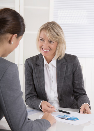 Two business woman sitting at desk: customer and adviser talking together. photo