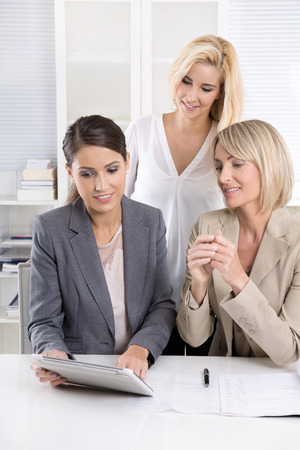 group  accountant: Team: Successful business team of woman in the office talking together looking at tablet computer.