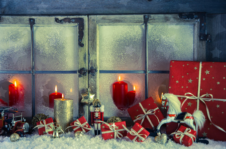 Classical xmas decoration in red and golden colors: rustic old wooden window with candles for a background. photo
