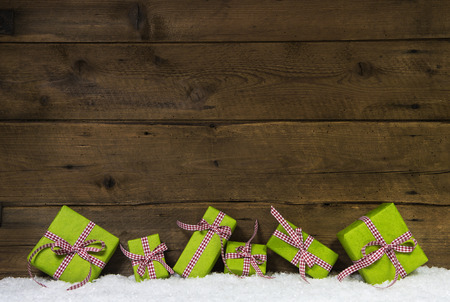 surprise gift: Apple green christmas presents with a red checked ribbon on wooden background for a gift certificate. Stock Photo