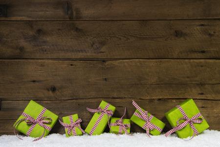 Pomme verte cadeaux de Noël avec un ruban à carreaux rouges sur fond de bois pour un certificat-cadeau.