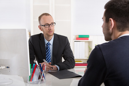 Two businessman sitting in the office: meeting or job interview situation. Stock Photo
