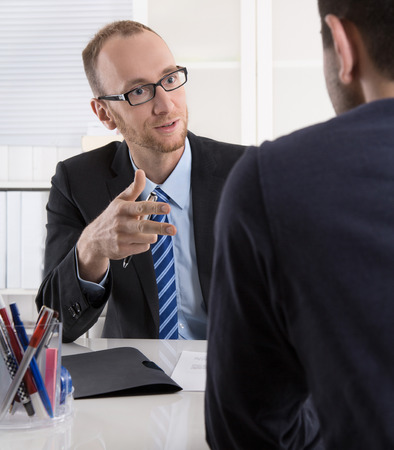 client meeting: Two businessman sitting in the office: meeting or job interview situation. Stock Photo
