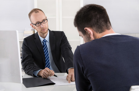his: Problems at workplace: boss critic his employee because of his behavior and rebuke him. Stock Photo